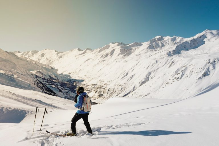 woman in skis standing on snow looking at the mountains